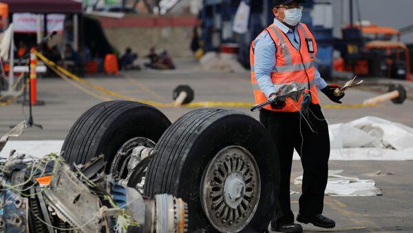Un funcionario de la Comisión Nacional de Seguridad del Transporte de Indonesia transporta escombros del vuelo JT610 de Lion Air, Indonesia - Sputnik Mundo