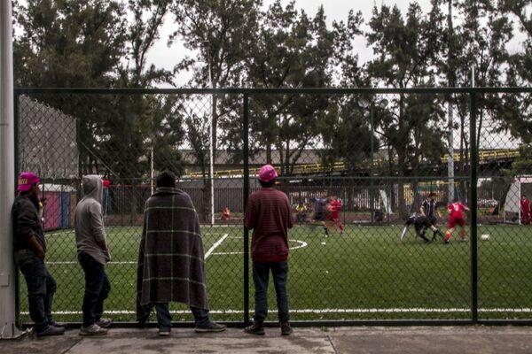 Integrantes del éxodo centroamericano miran un partido de fútbol entre Liverpool y Cuervos, en el deportivo de la Magdalena Mixhuca - Sputnik Mundo