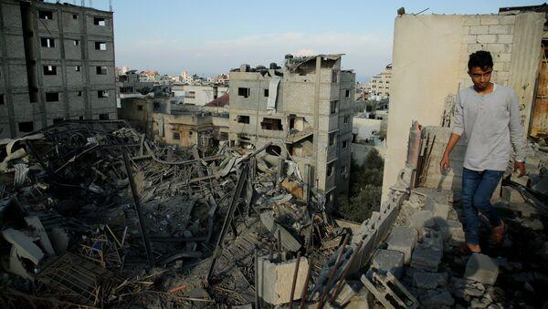 Un hombre camina en las ruinas de una edificación en Gaza - Sputnik Mundo