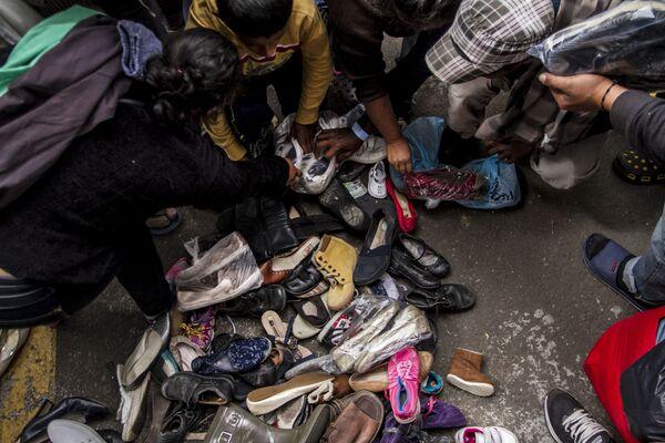 Integrantes de la segunda caravana del éxodo centroamericano buscan zapatos en buen estado que puedan utilizar - Sputnik Mundo