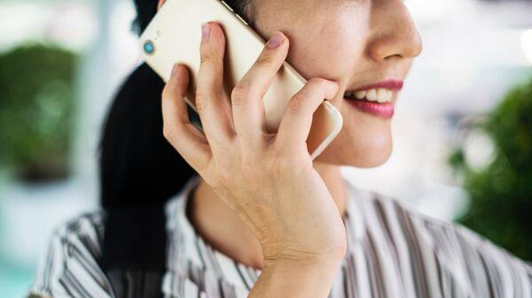 Una mujer hablando por teléfono móvil - Sputnik Mundo