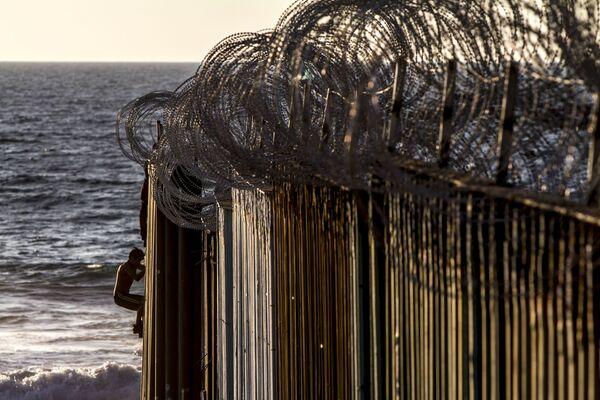 Dos jóvenes se suben al muro de playas de Tijuana después de que el Ejército estadounidense colocara alambre de púas el 13 de noviembre del 2018 - Sputnik Mundo