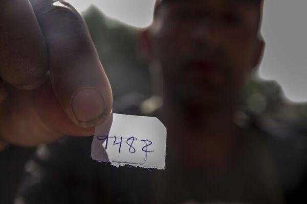 Billy Noel muestra el papelito que le dieron al pedir turno para solicitar asilo en el cruce fronterizo de San Ysidro - Sputnik Mundo