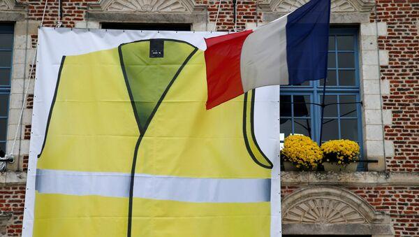 Un chaleco amarillo junto a la bandera de Francia - Sputnik Mundo