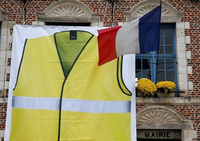 Un chaleco amarillo junto a la bandera de Francia