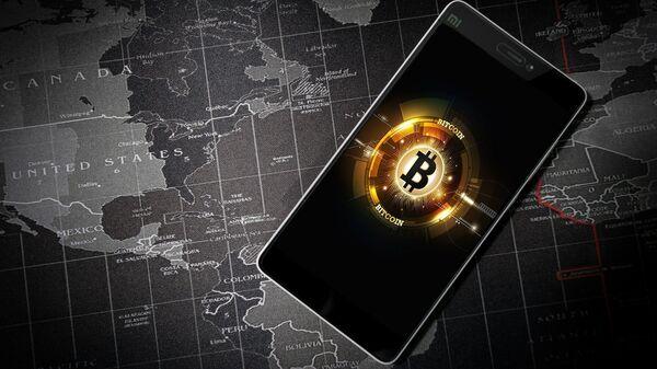 Un móvil con la imagen del logo de bitcóin   - Sputnik Mundo