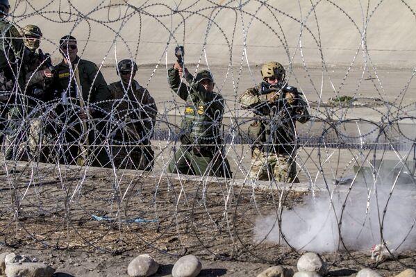 W. Lopez y D. Cody oficiales de la USBP (border patrol) disparan gases lacrimógenos contra la manifestación de centroamericanos en territorio mexicano - Sputnik Mundo