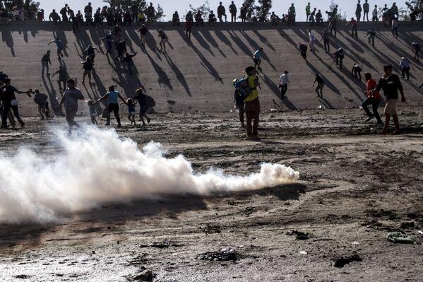 Manifestantes huyen del ataque con gases lacrimógenos de los elementos de la USBP (border patrol) al territorio mexicano - Sputnik Mundo