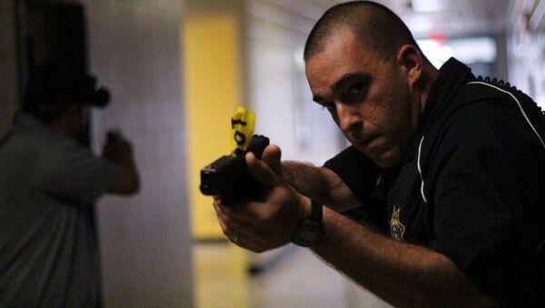 Un policía apunta un arma - Sputnik Mundo