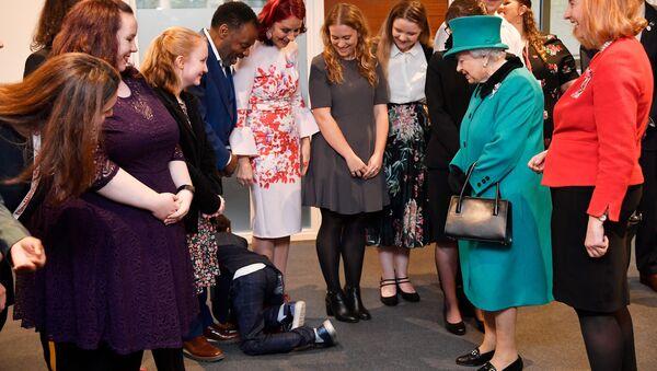 Un niño se arrastra mientras la reina británica Isabel visita la organización benéfica infantil Coram en Londres - Sputnik Mundo