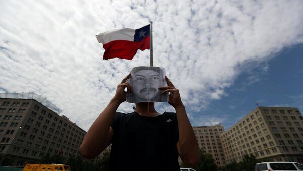 Un manifestante con el retrato del comunero mapuche Camilo Catrillanca - Sputnik Mundo