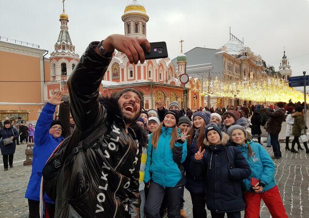 Escolares, durante una excursión por la Plaza Roja, posan para una foto con Tomer Savoia