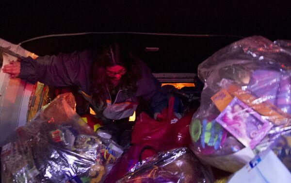 Voluntaria se prepara para repartir juguetes adentro de la camioneta del Loko - Sputnik Mundo