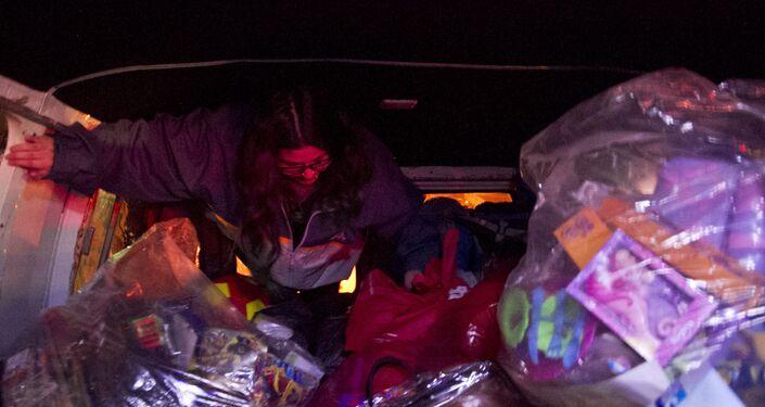Voluntaria se prepara para repartir juguetes adentro de la camioneta del Loko