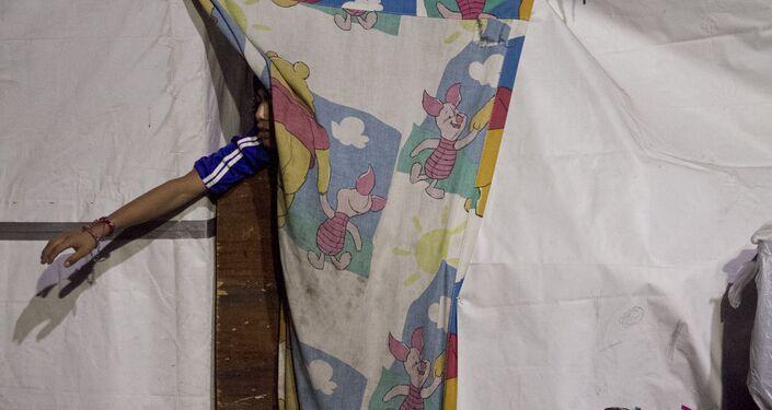 Niño en un campamento desalojado por elementos policiales recibe juguetes entregados por los reyes magos punks