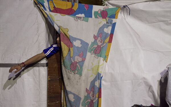 Niño en un campamento desalojado por elementos policiales recibe juguetes entregados por los reyes magos punks - Sputnik Mundo
