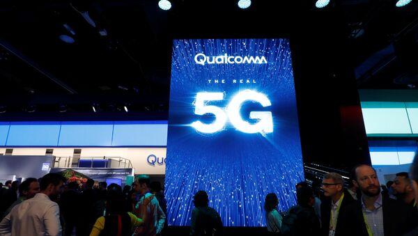 La gente pasa al lado de una pantalla que promociona la conectividad 5G en el stand de Qualcomm - Sputnik Mundo