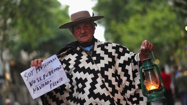 Un hombre sostiene una linterna en una marcha de protesta contra el incremento de tarifas en Buenos Aires - Sputnik Mundo