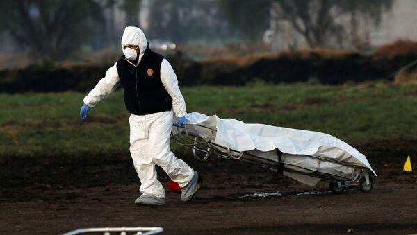 Un técnico forense en el lugar de la explosión en Tlahuelilpan, México - Sputnik Mundo