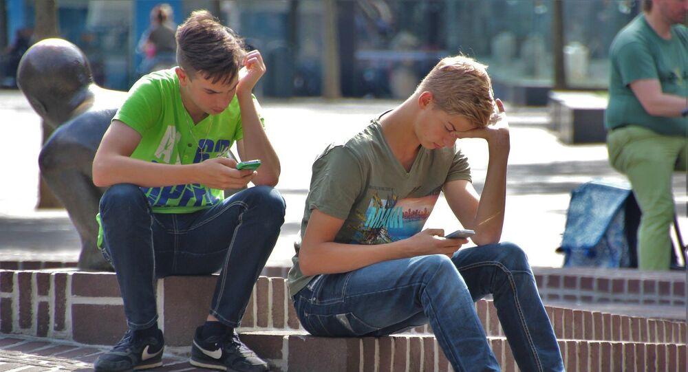 Jóvenes con sus celulares en una plaza