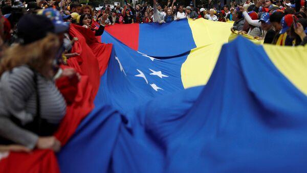 Personas con la bandera de Venezuela durante las protestas - Sputnik Mundo