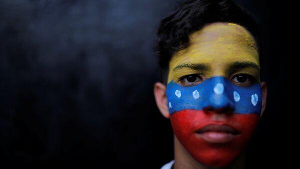 Un ciudadano con la bandera de Venezuela en su cara - Sputnik Mundo