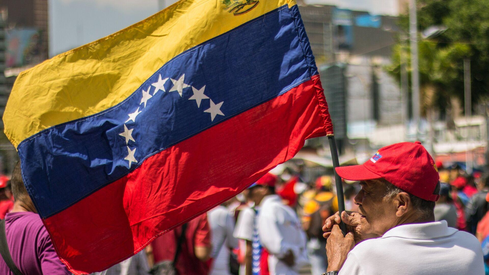 Un hombre con la bandera de Venezuela - Sputnik Mundo, 1920, 01.05.2021