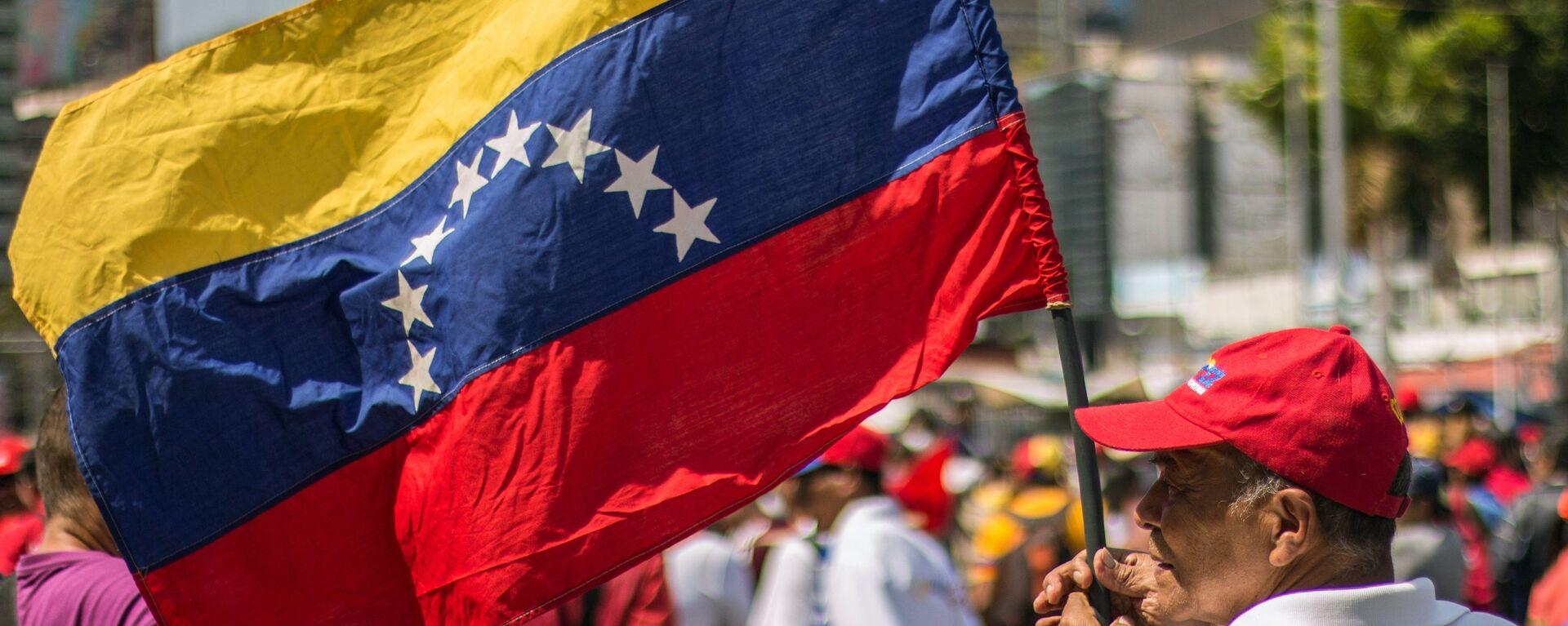 Un hombre con la bandera de Venezuela - Sputnik Mundo, 1920, 13.08.2021