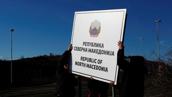 Obreros cambian carteles en un puesto de control fronterizo en Macedonia del Norte - Sputnik Mundo