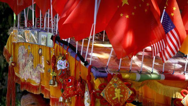 Un conductor mira desde su trishaw decorado con una bandera americana y una china en Pekín - Sputnik Mundo