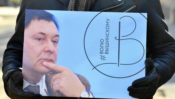 Un activista con la imagen del director del portal RIA Novosti Ukraina, Kiril Vishinski - Sputnik Mundo