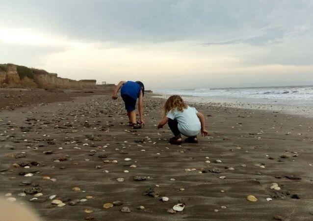 La pequeña Indira junto a su hermano en la playa Camet Norte, ubicada al centro sur de la provincia de Buenos Aires