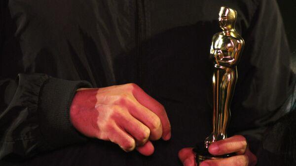 Vecino de la colonia Roma carga una estatuilla de los premios Oscar. - Sputnik Mundo