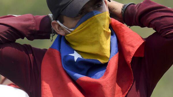 Un manifestante con la bandera de Venezuela en su cara - Sputnik Mundo
