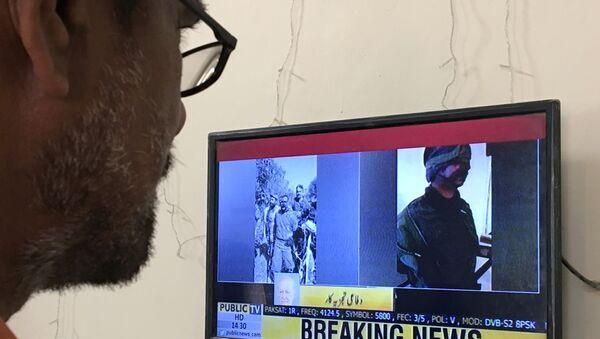Un hombre observa las noticias donde muestran al piloto capturado - Sputnik Mundo