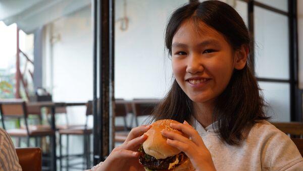 Una joven con una hamburguesa Durty Donald - Sputnik Mundo