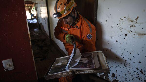 El bombero Leonard Farah rescata las pertenencias de las casas destruidas por el lodo tóxico, un mes después de la ruptura de una presa de la compañía minera Vale en Corrego do Feijao, cerca de Brumadinho, en el estado brasileño de Minas Gerais, el 22 de febrero de 2019 - Sputnik Mundo