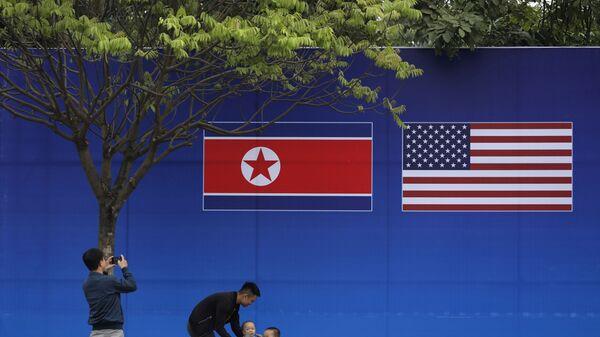 Жители Ханоя позируют перед изображением северокорейского и американского флага в дни прохождения саммита КНДР-США в Ханое - Sputnik Mundo