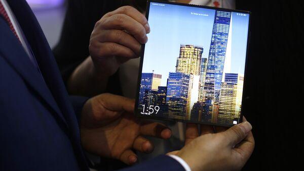 Un hombre sostiene un Mate X de Huawei durante el Congreso Mundial de Móviles  - Sputnik Mundo