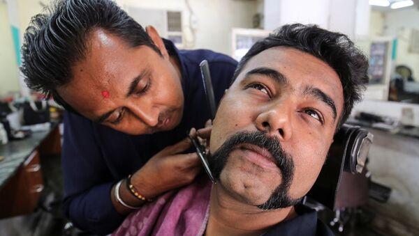Un hombre se corta el bigote y la barba como el piloto Abhinandan Varthaman - Sputnik Mundo