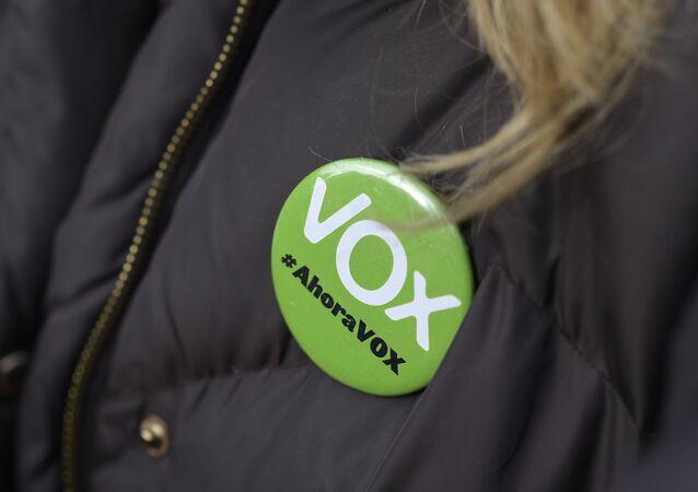 Una mujer lleva un alfiler que dice Vox, ahora