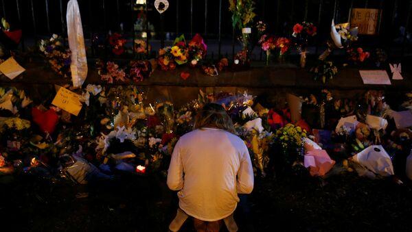 Un hombre reza cerca de la ofrenda floral a los víctimas del atentado en Christchurch, Nueva Zelanda - Sputnik Mundo