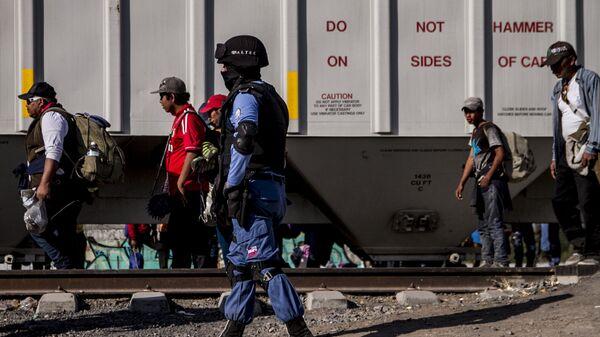 Seguridad privada vigila a migrantes frente a un tren de carga. En la ruta migrante se encontraron al menos cuatro de estas empresas dedicadas a la custodia de las vías, que también ejercen funciones de migración y seguridad pública. - Sputnik Mundo