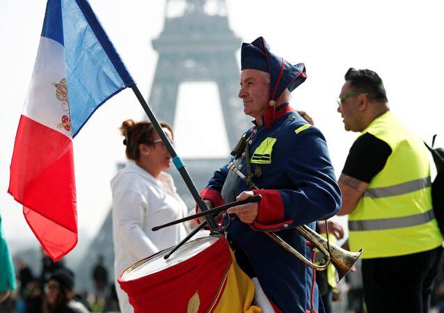 Hombre toca el tambor en la manifestación de los 'chalecos amarillos' en París