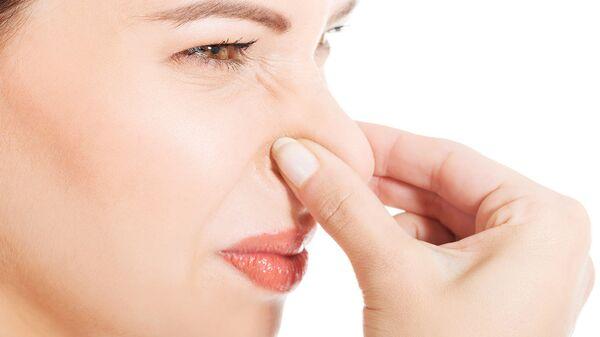 Mujer se tapa la nariz por el olor. - Sputnik Mundo