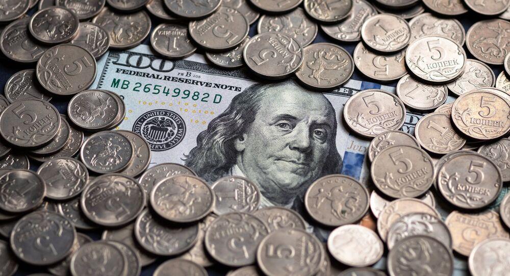 Monedas rusas y un billete de 100 dólares (imagen referencial)