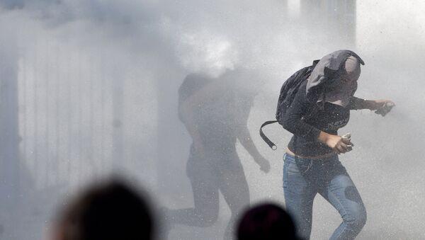 Manifestantes corriendo de la represión policial en el Día del Joven Combatiente de 2012 en Chile. - Sputnik Mundo