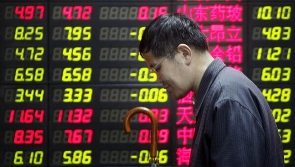 Un hombre cerca de una pantalla con precios en Shanghái - Sputnik Mundo