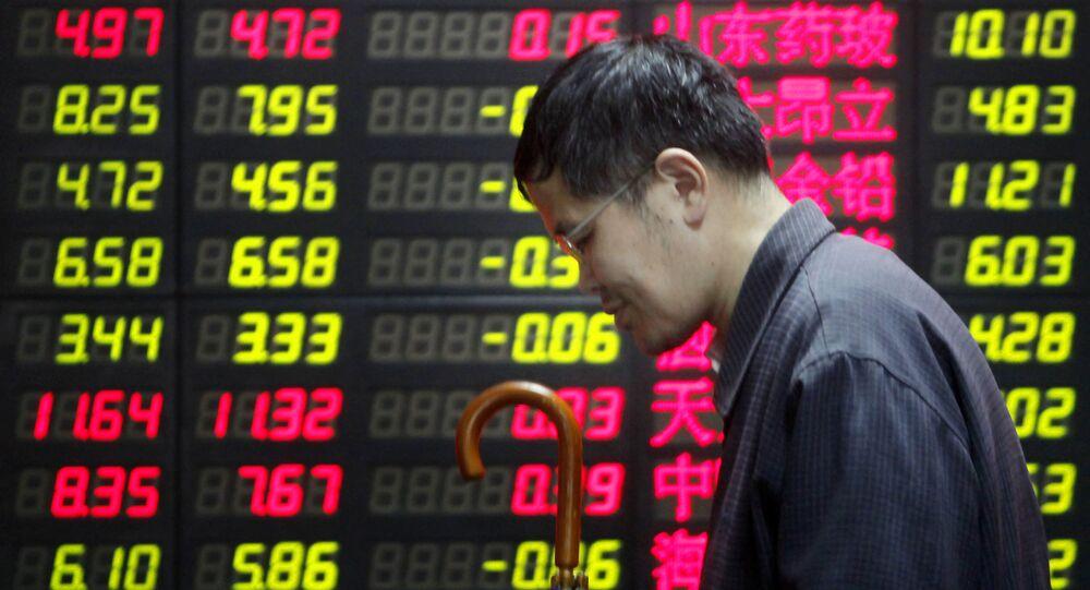 Un hombre cerca de una pantalla con precios en Shanghái