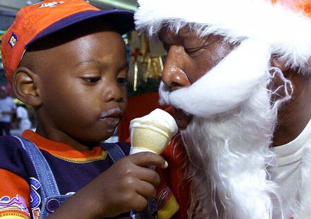 Un niño y Santa comen helado en Johannesburgo